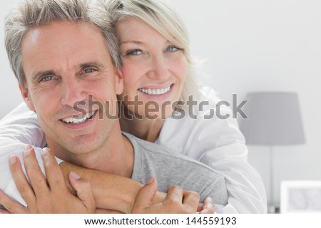 Affectionate couple smiling at camera at home in bedroom #144559193