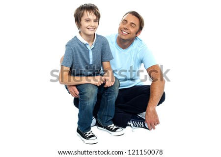 Affectionate father admiring his sweet son on his lap. Sitting on the floor, legs crossed. - stock photo