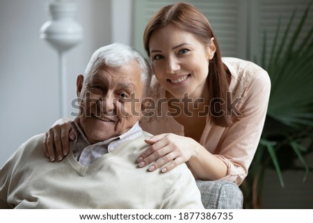 Photo of  Affectionate grownup daughter embrace retired elderly dad sharing optimism positive emotions. Tender young woman hug beloved old grandfather dreaming together of good happy future long healthy life