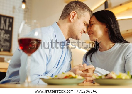 Affectionate. Handsome loving well-built man and a beautiful devoted dark-haired woman sitting with their eyes closed and holding hands while having romantic dinner #791286346