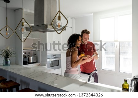 Affectionate interracial couple having healthy breakfast while on the mobile phone at home in the kitchen