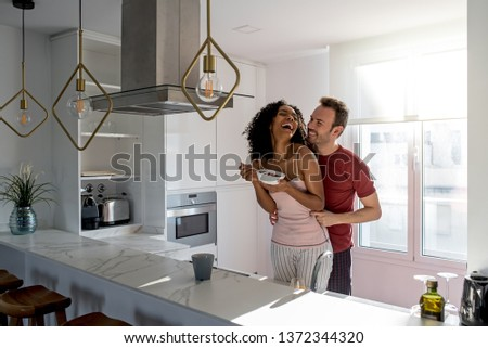 Affectionate interracial couple kissing while having healthy breakfast at home in the kitchen