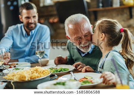Affectionate little girl kissing her grandfather while having family lunch in dining room.  stock photo