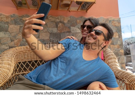 Affectionate lovers cuddling in an intimate moment touching and making a selfie with smartphone. Happy couple enjoying and smiling