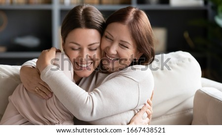 Affectionate loving middle aged mother cuddling grownup child, amazed by good news. Excited to see daughter, happy senior older mom cuddling her, sitting together on comfortable sofa in living room.
