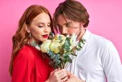 affectionate man offering his partner roses on pink background, lovely couple celebrating their anniversary, date or saint valentines day
