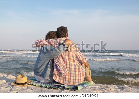 stock photo : Affectionate mature couple sitting close together at sunset on ...