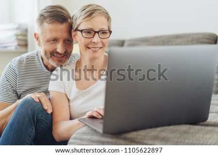 Affectionate middle-aged couple looking at a laptop together on a sofa in their living room browsing the internet or social media with a smile