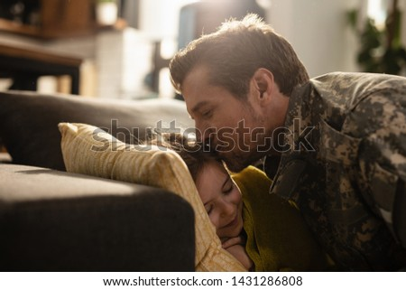 Affectionate military father kissing his daughter who is sleeping on the sofa at home.