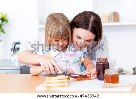 Affectionate mother helping her daughter prepare the breakfast in the kitchen