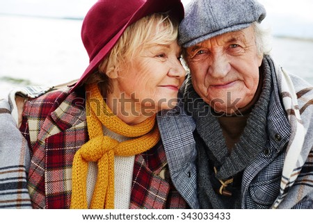 Affectionate senior couple in warm clothes