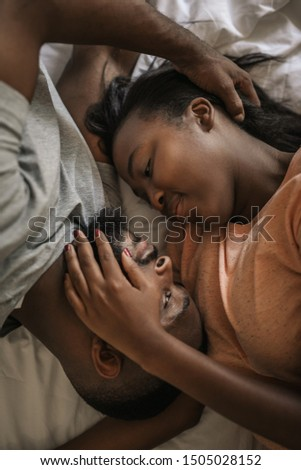 Affectionate young African American couple looking into each other's eyes while lying in bed together in the morning