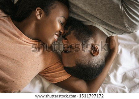Affectionate young African American couple lovingly kissing while lying face to face in bed together in the morning