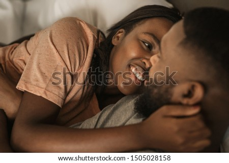 Affectionate young African American woman smiling and hugging her husband while lying in bed together in the morning