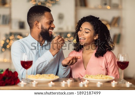 Affectionate young black couple having dinner, guy feeding his girlfriend with pasta. Cute lovers having romantic date, flirting, having fun, celebrating St Valentine's Day or holiday Stock fotó ©