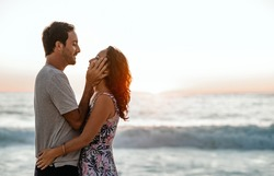 Affectionate young couple staring into each other's eyes while enjoying a sunset together at the beach