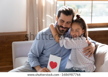 Affectionate young father hugging little child daughter, feeling grateful for birthday congratulations. Thankful daddy holding present, cuddling school aged small kid girl, fathers day celebration.