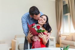 Affectionate young man giving his beautiful young wife a bouquet of red roses and kissing her on Valentines day , romantic happy couples sharing gift together on Valentines day