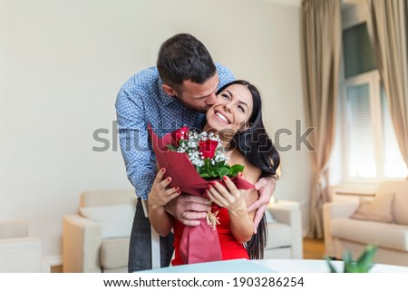 Affectionate young man giving his beautiful young wife a bouquet of red roses and kissing her on Valentines day , romantic happy couples sharing gift together on Valentines day ストックフォト ©