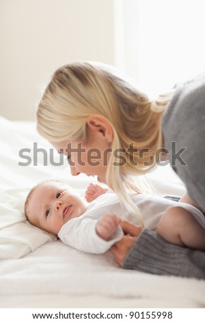 Affectionate young mom cuddling her newborn