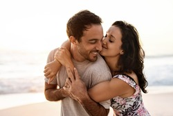 Affectionate young woman hugging her husband while having fun together on a sandy beach at sunset