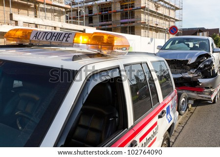 AFFOLTERN, SWITZERLAND-SEPTEMBER 15: Front car crash wreck sits on trailer at roadside to be hauled off by Autohilfe  in Affoltern, SUI on September 15, 2011.