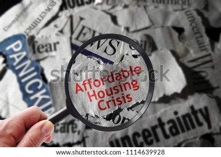 Affordable Housing Crisis newspaper headline and magnifying glass #1114639928