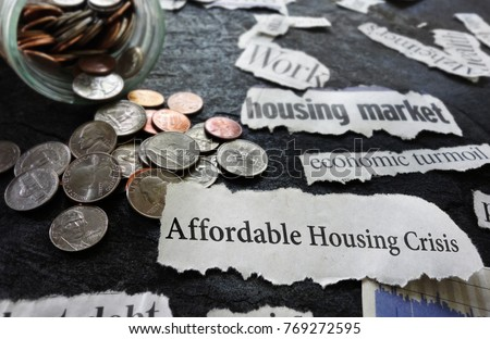 Affordable Housing Crisis newspaper headline and related economic news, with coins                                #769272595