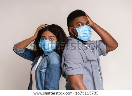 Afraid African American Couple Wearing Protective Face Masks And Holding Head With Hand, Panicking About Coronavirus Epidemy Over Light Background