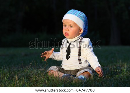 Afraid Baby boy with suit  sitting in scary forest. - stock photo