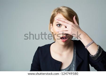 Afraid woman looking between fingers