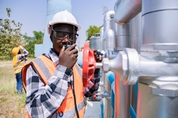 Africa American worker with assistant wearing safety goggles check condition of crude oil centrifugal pump and lube oil system. Metal lathe industrial manufacturing factory outside. Fix poblem