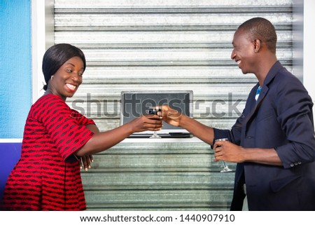 African adult businessman and adult woman speaking for business while drinking red wine while smiling outdoors
