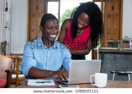 African amerian businessman at computer with woman indoor at home