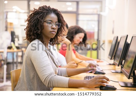 African American adult student working in computer class. Line of man and women in casual sitting at table, using desktops, typing. Staff training concept