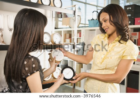 African-American and Asian women shopping for clocks in retail store. - stock photo