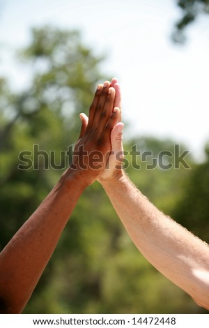 "african american and European american men do a ""high five"" hand clap outside"