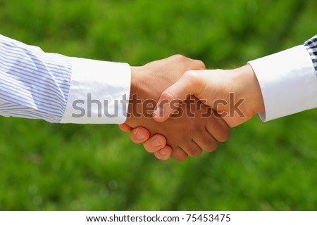 african american and European american men shaking hands with green grass on the background
