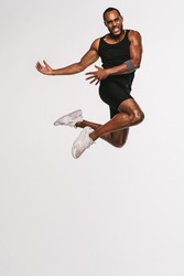 African american athlete doing fitness exercise. Fit man jumping high in air during workout.