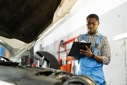 African American auto mechanic man in overalls and holding a notebook in his hands while standing near the open hood of the car