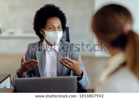 African American bank manager with protective face mask communicating with her client during a meeting in the office.
