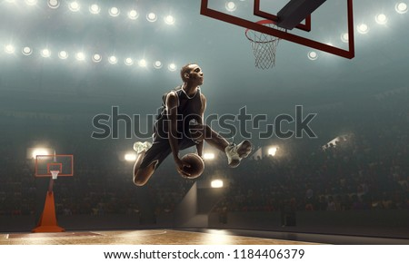 Photo of  African-american basketball player scores a goal during a game on a professional basketball arena