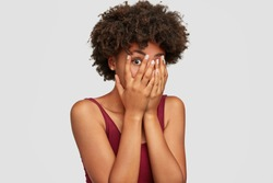 African American beautiful young female peeks though fingers, covers face with both hands, has frightened expression as notices something terrible or scarying, isolated over white background.
