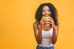 African American black beautiful young woman eating hamburger isolated on yellow background.