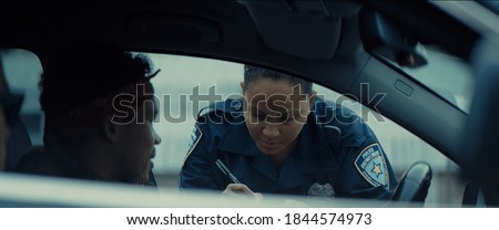 Photo of  African-American black driver is being pulled off by mixed-race female police officer. Documents check, speeding ticket
