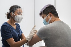 African American Black female Doctor prepares to administer vaccine to a Chinese patient in vaccination cabin. COVID-19 coronavirus vaccination