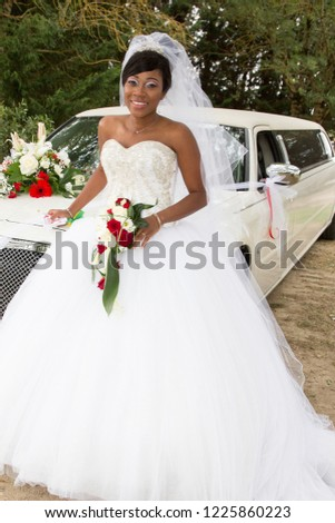 African-American black woman in white wedding dress with limo car