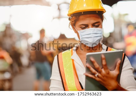African American black women teen worker wearing face shield or disposable face mask during working in factory for prevent spreading of Coronavirus(Covid-19) and air dust pollution for labor healthy. Foto stock ©