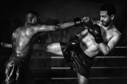 african american boxer making yap punch in defencing to caucasian boxer making yap in muay thai or kickboxing fighting match in black and white