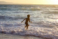 African american boy frolic and swimming in the sea